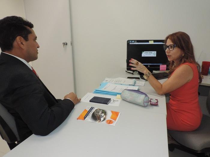 Promotora de Justiça Denise Aguiar diante do computador, ao lado do Procurador-Geral de Justiça. Na tela do computador, pode se ler