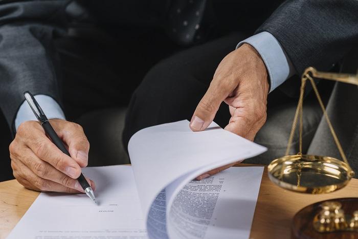 Mão de uma pessoa assinando um documento sobre uma mesa