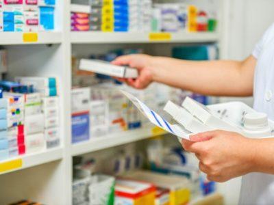 Fotografia que mostra as mãos de um profissional de saúde, arrumando caixas de medicamentos em uma estante