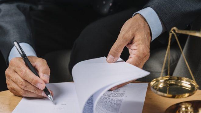 Imagem da mão de uma pessoa assinando um documento sobre uma mesa. Ao lado há uma balança representando a Justiça